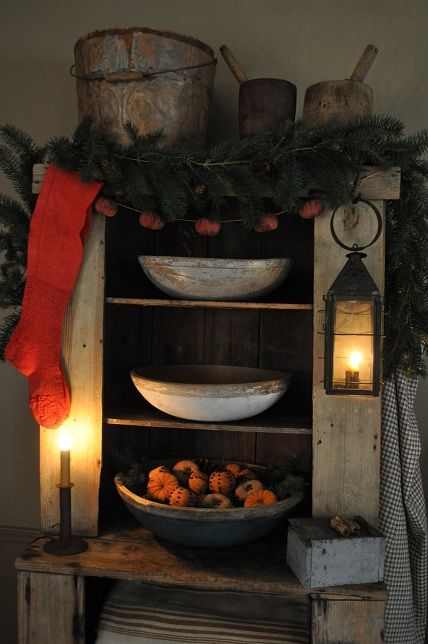 Old distressed cupboard filled with needful things...old wooden bowls, pine, old wood buckets, grungy lanterns...red stocking.