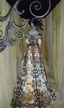 House of Worth evening dress (ca. 1898-1900) has a skirt and bodice of white silk satin and silk voided velvet, its lines reminiscent of swirling French wrought iron and the paintings of Erté.