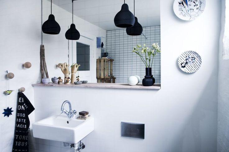 Den ene baderomsveggen er flisebelagt med små hvite fliser, mens resten av rommet består av hvite murvegger. Badet har ikke et baderomsmøbel, men bare en enkel vask, og en trehylle under speilet. Belysningen består av to svarte taklamper som henger ned inntil speilet. FOTO: Tia Borgsmidt