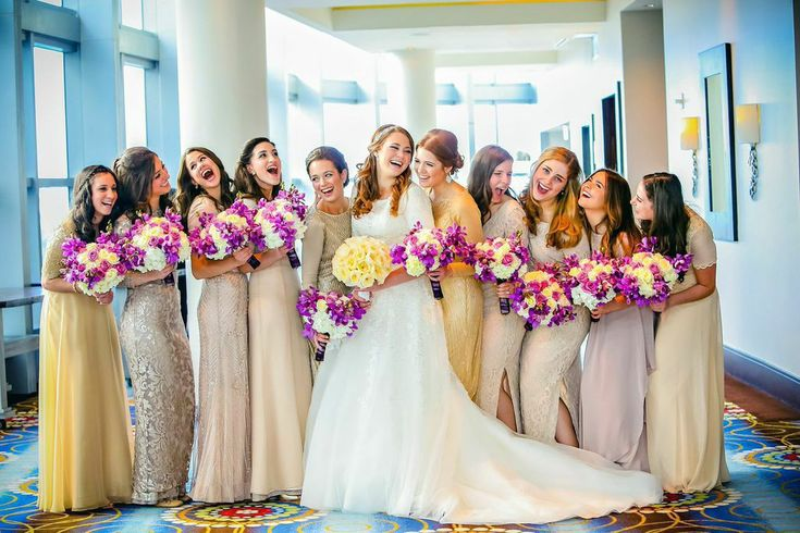 Mismatched bridal parties who get an A-plus for execution. This bridal party's look works because they established a base tone for their floor-length gowns. The bride gave her bridesmaids champagne color swatches and asked them to find dresses in the same color family.
