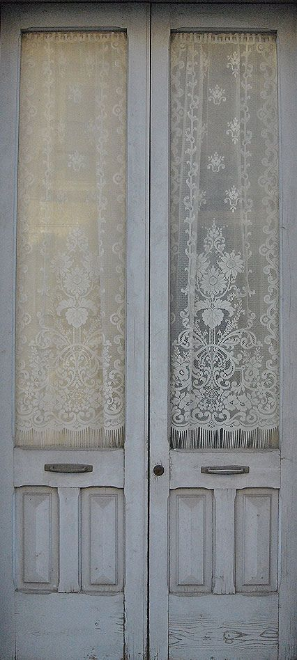 I love these lace curtains on the antique doors.
