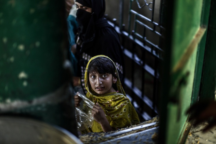 June 7, 2013. A Pakistani girl looks through a window of a food distribution center hoping to receive a ration of rice at a shrine in Islamabad. Photo by Muhammed Muheisen, AP.