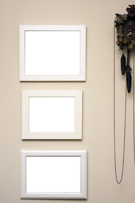 Three empty frames hanging on a beige colored wall alongside a wooden carved cuckoo clock with pendulums - free stock photo from www.freeimages.co.uk