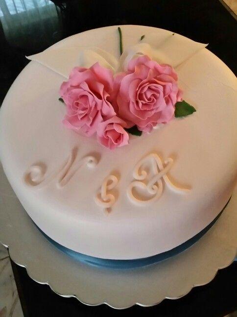 Pastel de aniversario con la cubierta de crema chantilly , las flores y el lazo son de fondan .               Pastel de aniversario con la cubierta de crema chantilly , el lazo y las flores son de fondant.