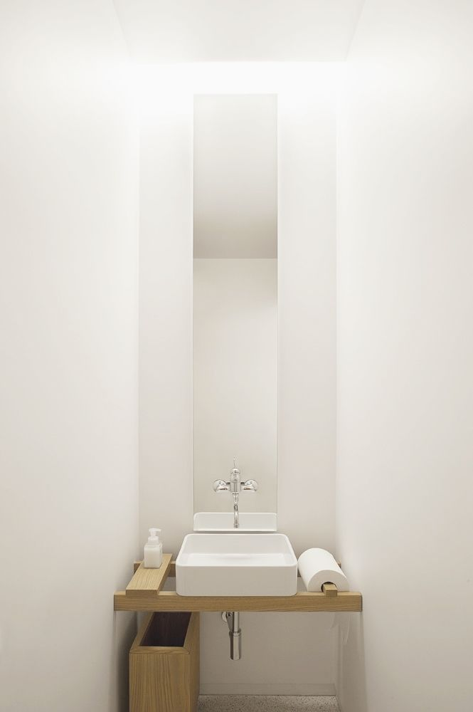 Minimalist powder room with large metal basket of toilet for Ordenadores para cocina