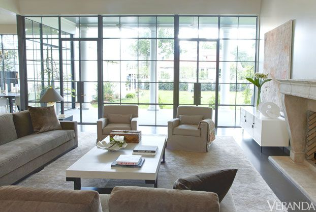 Metal mullions on custom windows have a bronzed finish for a subdued effect. Cocktail table, Christian Liaigre. Sofa, Christian Liaigre, in John Hutton Textiles mohair. Custom chairs in John Hutton Textiles mohair. Stone fireplace, Formations. White lacquer credenza, BDDW. Lamp, Donghia. Rug, Stark. Windows and doors, Crittall.   - Veranda.com