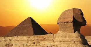 La esfinje de Guiza Egipto a la puesta del sol con la piramide de Queops la mas alta del mundo.