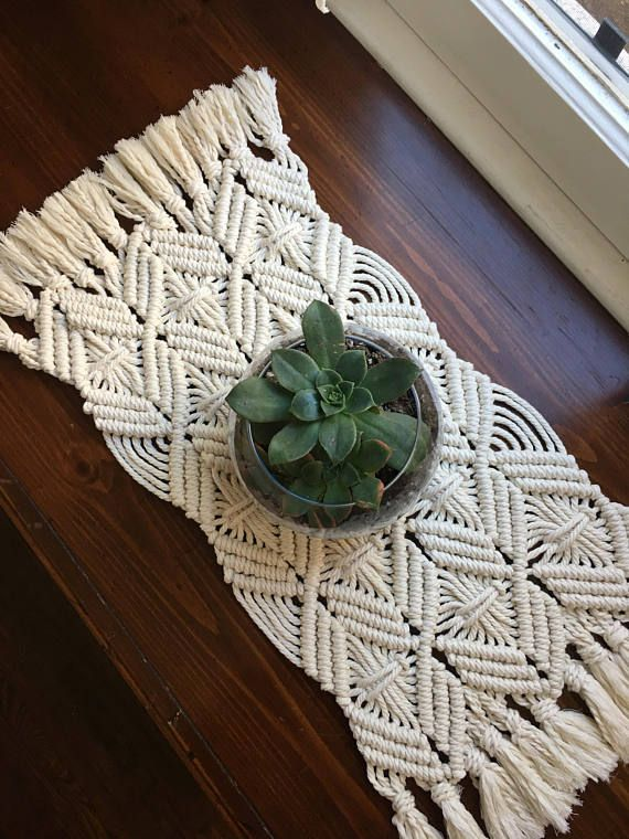 A modern macrame table runner or placemat made with 4 mm natural cotton rope. This table runner features diamond shaped knots and lots of fringe tassels on each end. It is a clean modern way to dress up your dining room table or really any table in your home. I love the look with a