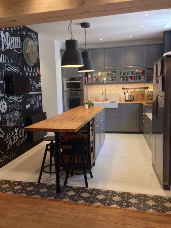 W całkiem przestronnej kuchni na środku przeznaczono miejsce na wyspę z drewnianym blatem. Ciemne szafki oraz ściana...
