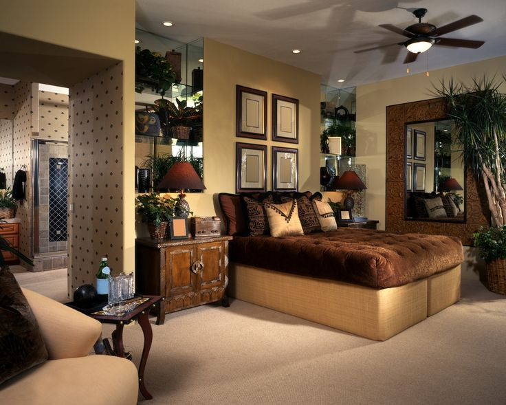 Ornately decorated bedroom with wall art, plants, pillows and custom wood furniture.
