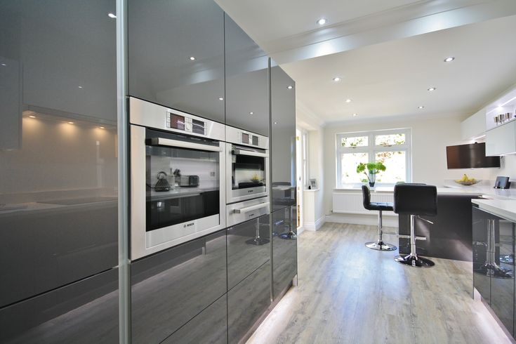 Modern White and Grey Acrylic Kitchen Design with Eye level BOSCH Appliances. Designed, Supplied and Installed by Kitchencraft Essex.