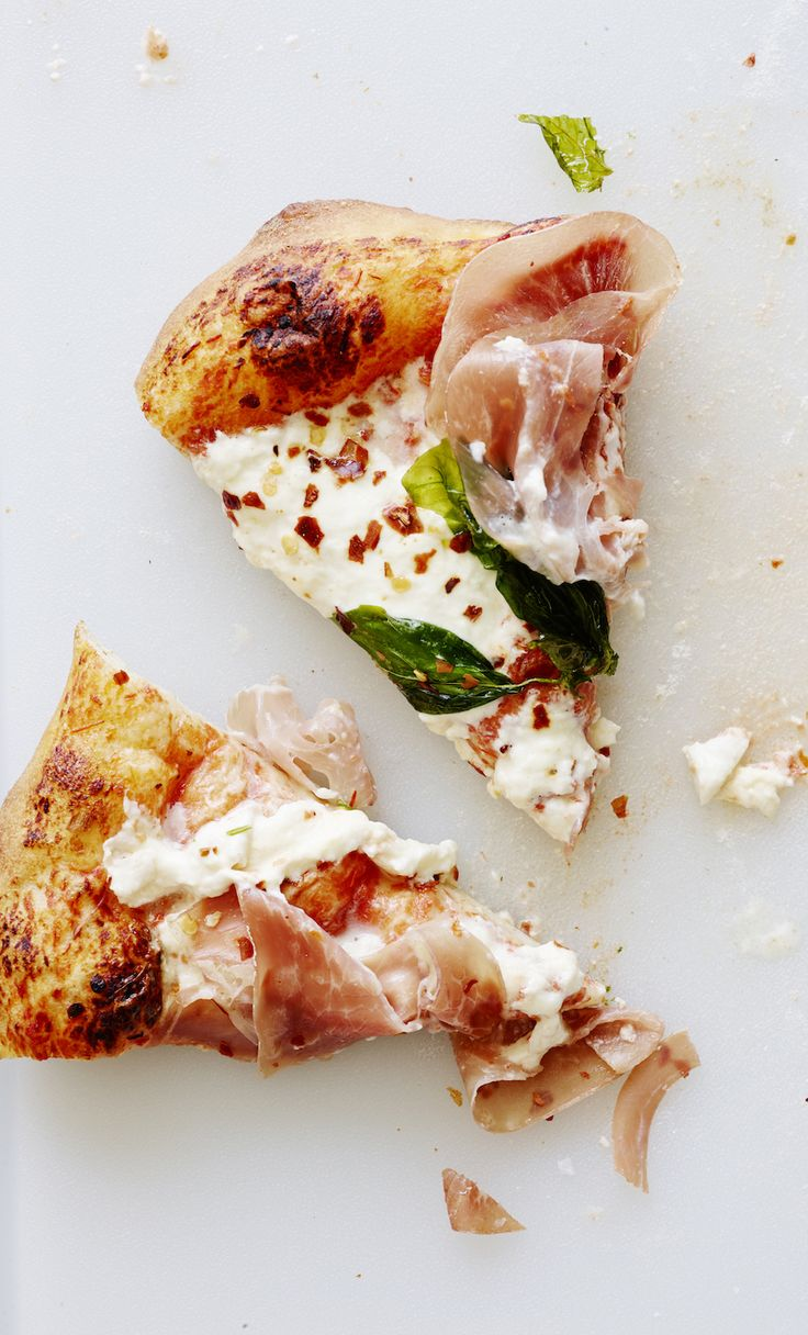 Burrata Pizza topped with fried basil, red pepper flakes and prosciutto