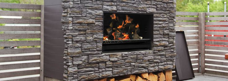 Escea EW5000 outdoor wood fireplace and bbq on a deck without a stainless steel fascia with a stack stone wall & a wood stack. #hwhs #hotwaterandheating