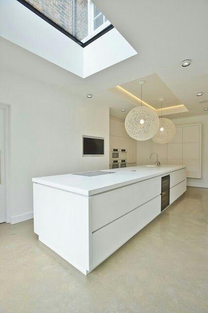 cocina minimalista blanca con isla central para fregadero y zona de cocción, módulo empotrado, tragaluz, suelo microcemento