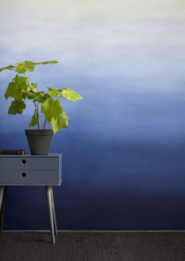 Verdeel je muur denkbeeldig in 3 tot 4 (ongelijke) horizontale banen. Meng een deel van je verfkleur in 2 tot 3 tinten naar wit. Zorg dat je in 1 keer voldoende mengt voor je muur. Breng met een roller aan de onderzijde van de de muur een baan aan in de volle kleur. Verf de banen opzettelijk grof en ongelijk om een natuurlijk verloop te creëren. Na het aanbrengen van de tweede tint, breng je met behulp van een plantenspuit en een kwast (of spons) een vloeiend verloop aan tussen de 2…