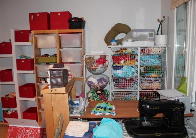 Laatikoissa vaatteita, kankaita ja kuvassa 2 konetta ja pakkauspöytä