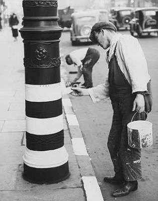 World War 2: Painting lamppost and kerbstones in Leicester to assist road users during a black-out rehearsal. January 26, 1938 ~