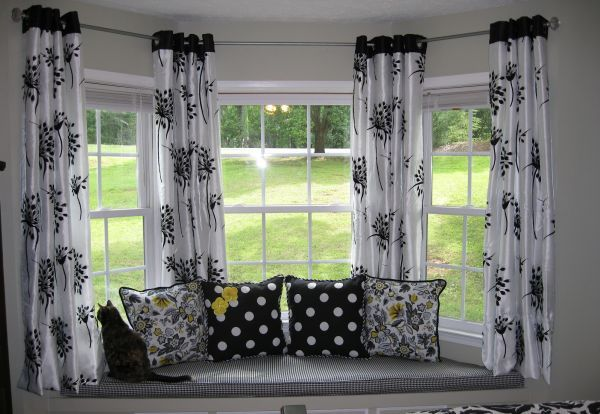 The best window treatments for bay windows are those that don't block the beauty of the windows at all. These curtain panels when open hang between the three windows so no light is blocked at all.  This is also the perfect idea if your bay window has a window seat.  We are a Minneapolis MN replacement window company.  www.replacementwindowsmpls.com