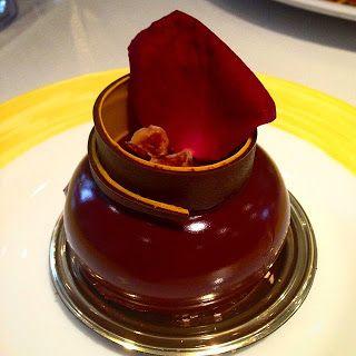A base em mousse é composta por uma esfera levemente achatada, sobre a superfície, o reflexo das luzes do teto incidem e deixam-na brilhante. No topo, um rolo deitado que finaliza em curva e em ponta, constituído de duas finas camadas, a parte interna, de massa de nozes com creme e a outra, de pralinê de avelã. No interior do rolo, dois pedacinhos de chocolate partidos na base de uma pétala de rosa vermelha que enfeita e escora-se em parte do rolo.