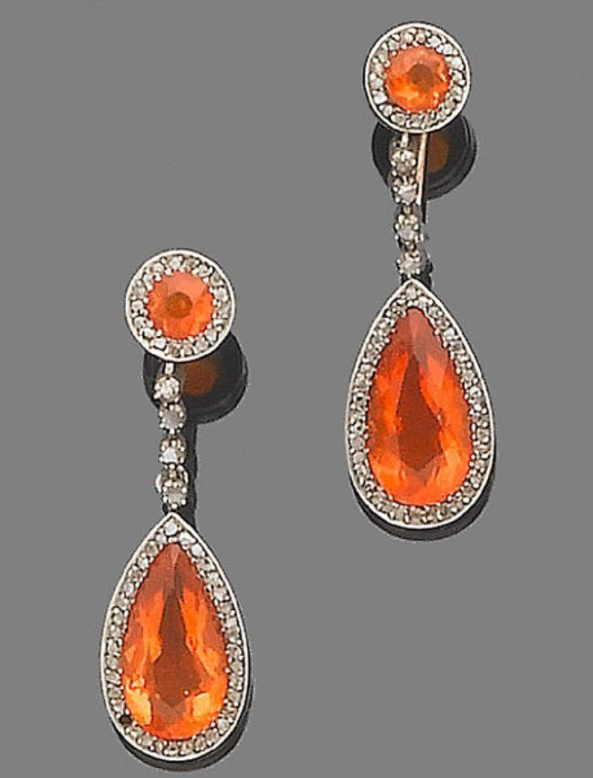 A pair of fire opal and diamond pendent earrings, circa 1900  Each circular mixed-cut fire opal surmount, within a rose-cut diamond surround, suspending a similarly-cut diamond line, terminating in a similarly-set pear-shaped fire opal drop, later hoop fitting, one diamond deficient, length 3.7cm., cased by Sanders, 43-45 High Street Kensington