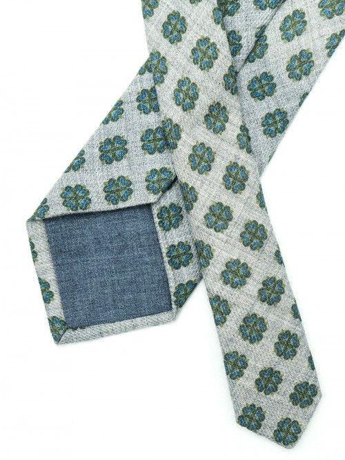 Corbata de lana confeccionada en Italia de manera artesanal siguiendo la tradición italiana. Corbata de 8 centímetros de ancho de pala, en diseño melange con diseño de flores geométricas en tonos azul y verde. www.soloio.com  #soloio #soloiomioda #shoponline #tie #corbata #menstyle #bespocke #suitup
