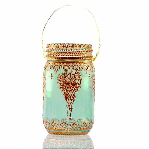 Aqua Mason Jar Lantern with Moroccan Styled Copper Detailing  This unique lantern takes the mason jar to a whole new level! Perfect for adding home crafted elegance to any event, from a lavish wedding to an evening dinner on your own patio. These lanterns can withstand outdoor conditions- stands up great to wind and rain. A collection of these strung up on a warm spring night could be a wonderful alternative to the usual paper lanterns- adding colorful mood lighting in a lavish new way…