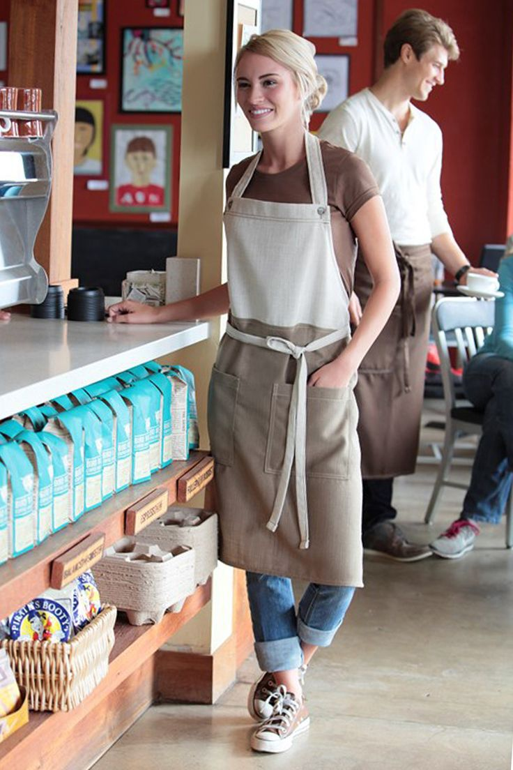 The Soho bib apron. Natural/camel colour. The perfect combination of edgy fashion and forward-thinking functionality. Featuring a contrast color block, buttoned neck strap, reinforced stress points and two patch pockets. Perfect for any kitchen, cafe or restaurant.
