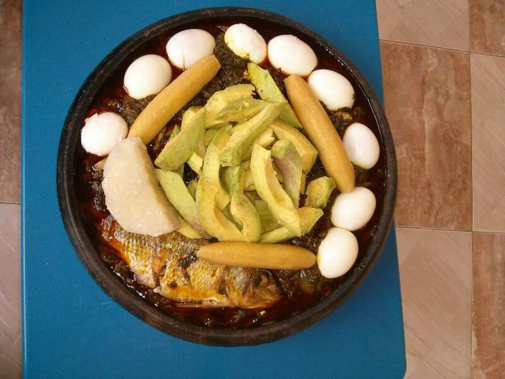 Kontomire fro-ye in red oil, cooked yam and plantain, boiled eggs, tilapia
