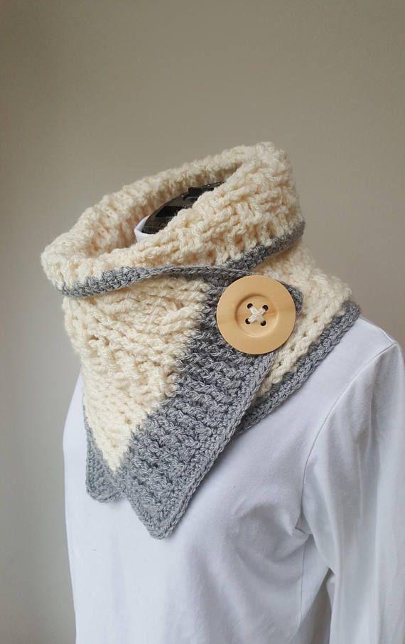 This crochet neckwrap is an extremely versatile little scarf. With a detachable button fastening, you can arrange the scarf any which way you like and feed the button fastening through any stitch of the scarf to hold it in place. One half of the scarf is made in Aran stitches (cables