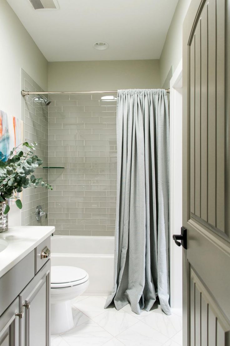Split shower curtain ideas - Luxurious Layers Of Gray Paired With An Abstract Art Piece To Give This Bathroom A Sophisticated