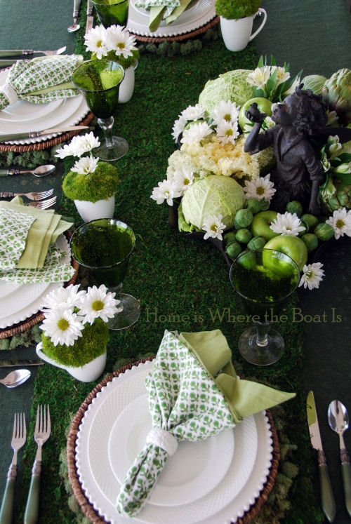 Green and white tablescape using moss,  white flowers, and green fruits and veggies.