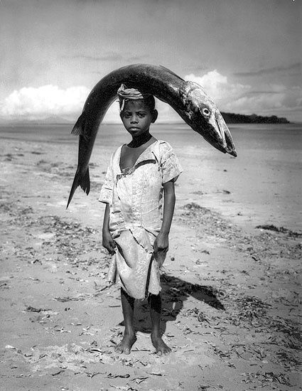 black children holding barracuda fish