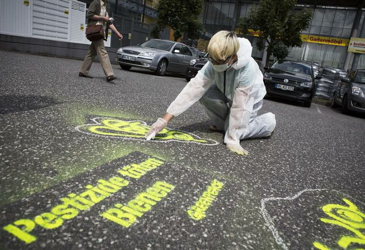 "Greenpeace activists protest during a Greenpeace group action day in fifty German cities at three big hardware store chains (Obi, Praktiker and Toom) against the sale of bee-harming insecticides. The photo shows activists in Hamburg in front of the hardware store ""Max Bahr"" spraying and painting the outline of dead bees on the tarmac , displaying a slogan reading: ""Pesticides kill bees!"" © Maria Feck / Greenpeace"
