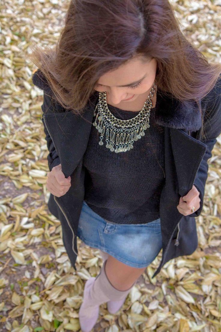 Collar plateado con toques negros en conjunto con botas caña alta saco de lana y abrigo largo.