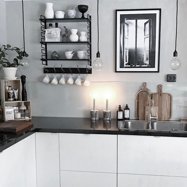 Black and white kitchen with wood details and framed poster of a window, from printler.com the marketplace for photo art. Interior design by lapptussan at instagram, motif by Annika Öhman. Available at https://printler.com/sv/foto/9446