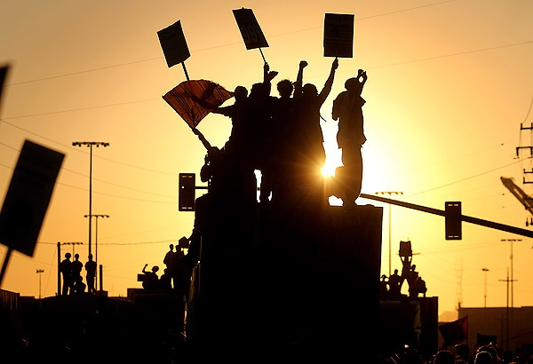 OAKLAND -  Occupy Oakland protesters cheer as they climb on tractor-trailers loaded with shipping containers at the Port of Oakland, effectively shutting down the United States' fifth-busiest port during a day of nonstop protesting.  ( Kent Porter / Santa Rosa Press Democrat / November 2, 2011 )