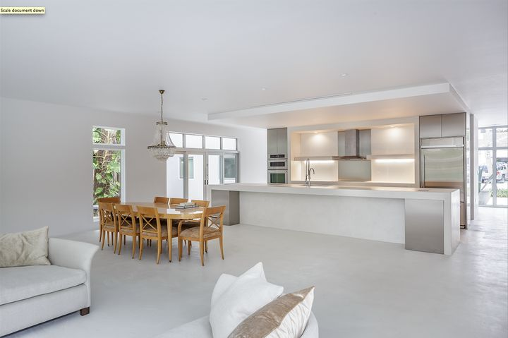 Set against a polished white backdrop, the wood dining table and chairs positively pop at this concrete and granite home in Florida.     This originally appeared in Passive Materials Cool this Bright White Tropical Home.
