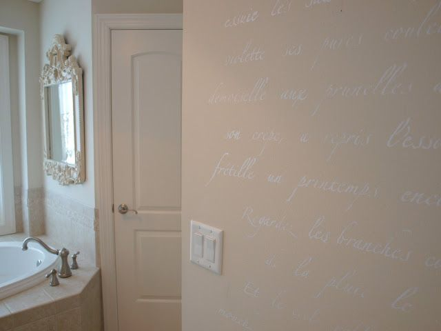 Detail of stenciled wall in master bathroom with French poem stencil/antique painted mirror above soaking tub/Benjamin Moore White Sand painted walls/Hello Lovely Studio