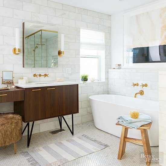 Retro and modern meet to create a tranquil yet edgy master bathroom. Brass accents repeat throughout the room, including a faucet, sconces, cabinet hardware, and the shower frame, reflect in a streamlined mirror. Hairpin legs on the vanity complete the midcentury-modern look./