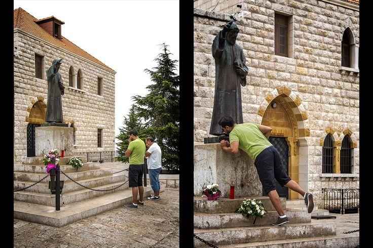 Mężczyźni modlący się przed figurą św. Charbela na placu przed klasztorem.