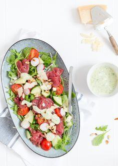Dit is lekker carpaccio salade. Supermalse carpaccio, echte Parmezaan, verse tomaatjes uit het seizoen en een romige pesto-dressing.