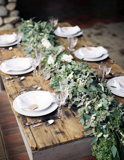 bare wood, greenery off table, and simple place settings.