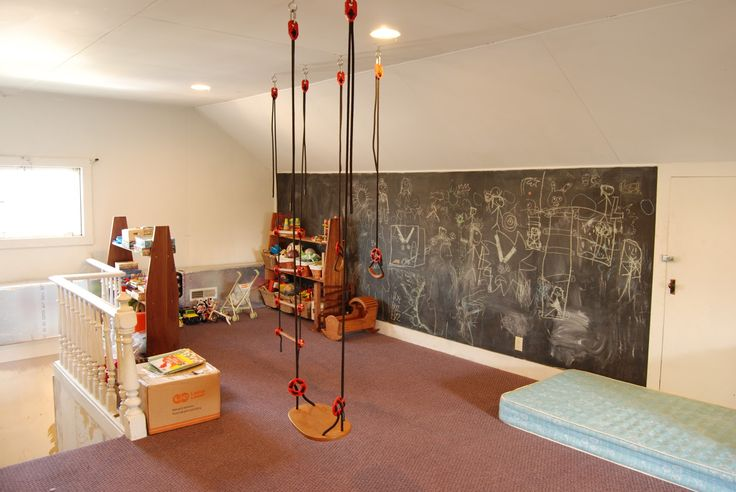 A very functional rumpus room.  Place for kids to draw, swing, climb, jump on a mattress, in a finished attic room.