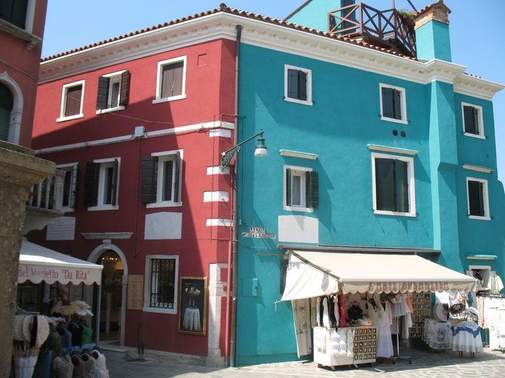De twee kenmerken van Burano bij elkaar: kleurig geschilderde huizen en de verkoop van kant. In sommige dure zaken kun je nog authentiek kant kopen, gemaakt door oude vrouwtjes die druk aan het kantklossen zijn in of voor de winkel.