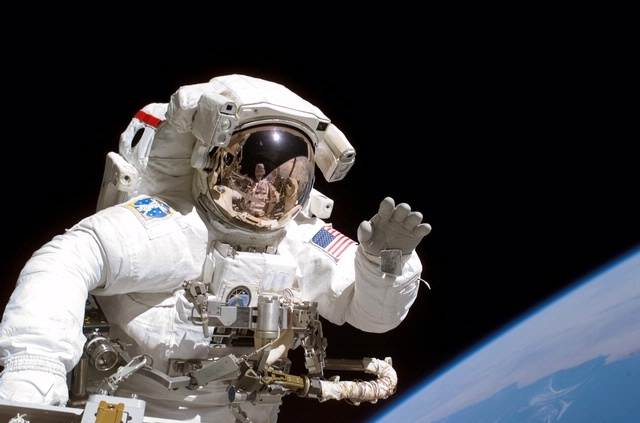 September 12, 2006. Astronaut Joseph R. Tanner, STS-115 mission specialist, waves toward the digital still camera of his space walk colleague, astronaut Heidemarie M. Stefanyshyn-Piper as the two share extravehicular activity (EVA) duties during the first of three scheduled spacewalks. Photo credit: NASA