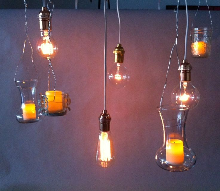 An eclectic mix of suspended vintage-style light bulbs and LED votive candles in various styles of glass containers.