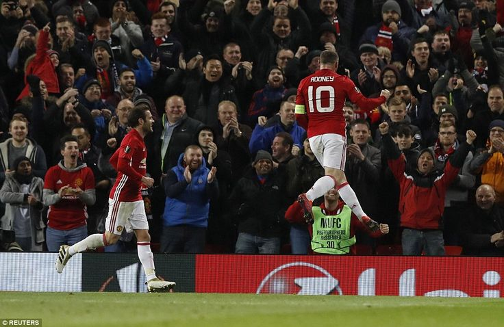 Rooney flies through the air and clenches his fist as United's supporters join in the cele...