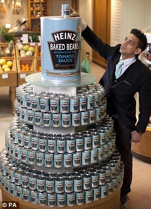 Sales assistant Hitesh Motwani helps launch the Heinz limited edition vintage 1952 label beans cans for the Queen's Diamond Jubilee at Fortnum & Mason.