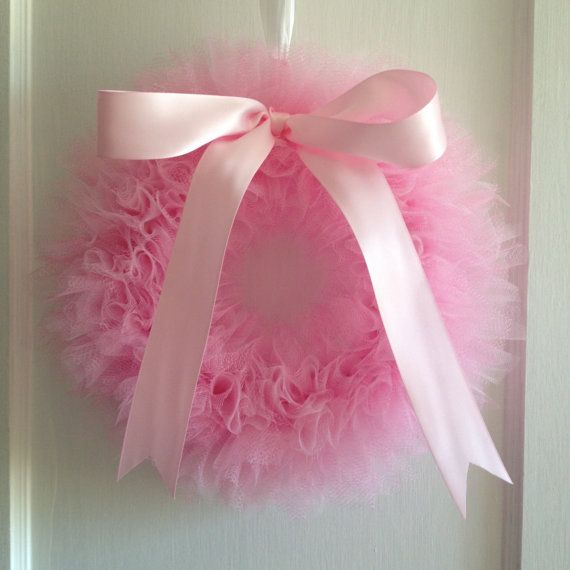 The wreath is tied with layered light pink and paris pink tulle. It is finished off with a pink satin bow. A loop is located on the back to easily