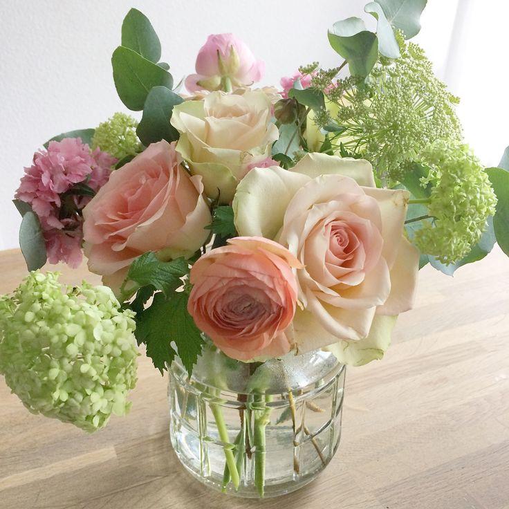 Heerlijk boeket in pastel tinten met ranonkels rozen viburnum enz